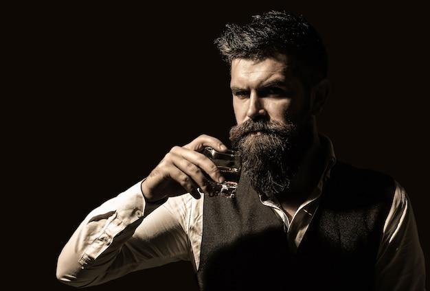 Uomo con in mano un bicchiere di whisky. sorseggiando whisky. l'uomo con la barba tiene il brandy di vetro. bere da macho. degustazione, degustazione. bevanda barbuta cognac. il sommelier assaggia la bevanda. ritratto di uomo con barba folta.