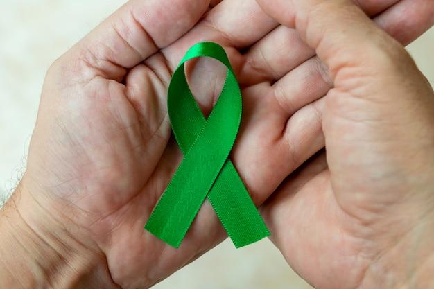 Uomo che tiene un nastro verde sul palmo della mano per sostenere le persone che vivono e le malattie.