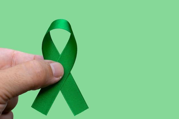 Uomo che tiene un nastro verde. concetto di mese di consapevolezza del cancro di fegato, cistifellea, reni e linfoma.