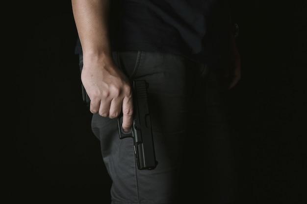 Uomo che tiene la pistola vicino al corpo, killer con pistola da 9mm in attesa di rapinare la vittima