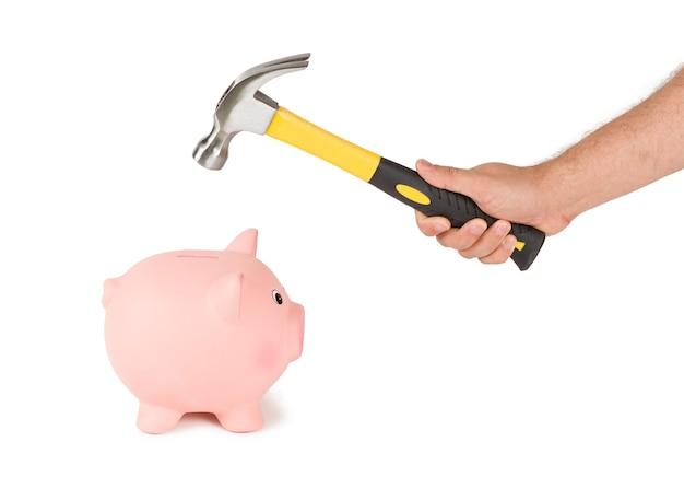 Uomo che tiene un martello e una grande banca. rompere il concetto di risparmio.