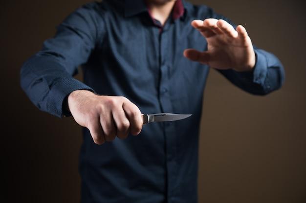 Uomo che tiene in mano un coltello su una superficie marrone