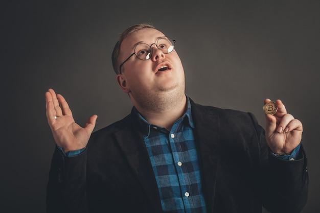 Uomo che tiene in mano il simbolo della valuta cripto bitcoin e che dice grazie a dio