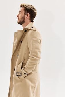 Uomo che tiene le mani nelle tasche del cappotto beige vista laterale sfondo chiaro