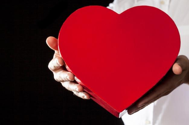 Un uomo che tiene una confezione regalo di cuore in un gesto di dare.
