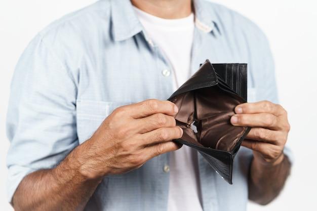 Uomo che tiene il suo portafoglio vuoto su sfondo bianco crisi finanziaria fallimento senza soldi