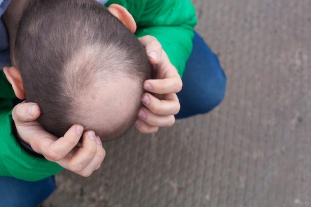 Uomo che tiene la testa tra le mani seduto sul pavimento squat. disperazione, depressione, concetto di disperazione. Foto Premium