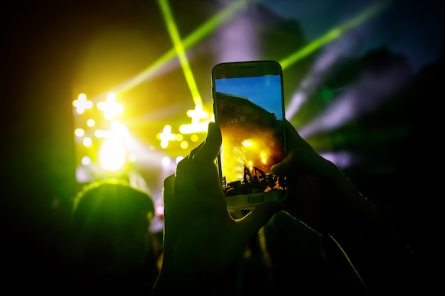 Uomo che tiene il suo smart phone e fotografare un concerto.