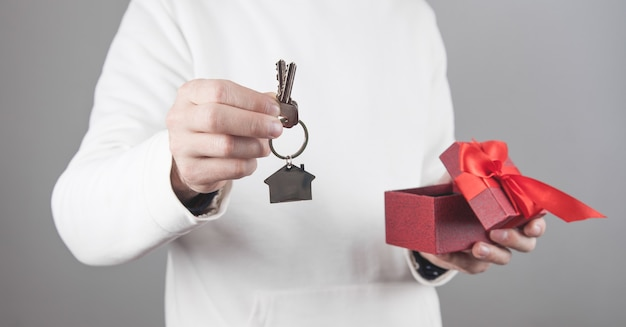 Uomo che tiene casa e chiavi con confezione regalo.