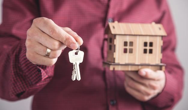 Uomo che tiene le chiavi di casa con il modello di casa in ufficio.