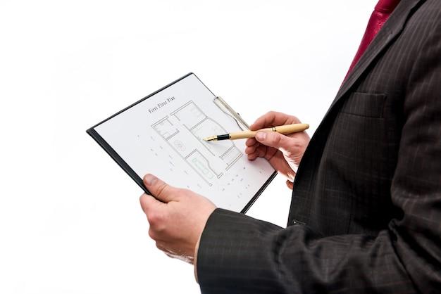 Uomo che tiene il piano della casa con appunti sul muro bianco
