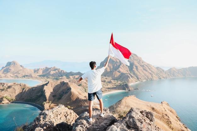 Un uomo con la bandiera dell'indonesia a labuan bajo