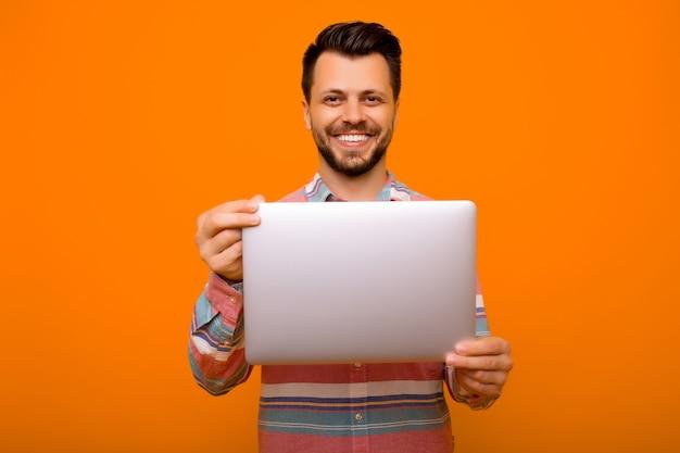 Uomo che tiene il computer portatile e sorride alla macchina fotografica.