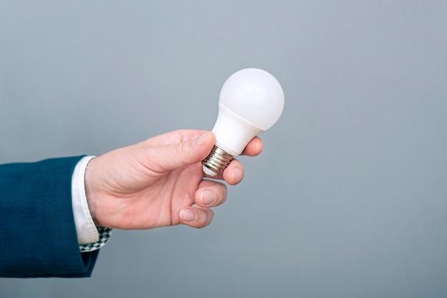 Un uomo che tiene in mano la lampadina a led. immagine di concetto su economia, elettricità e risparmio di denaro