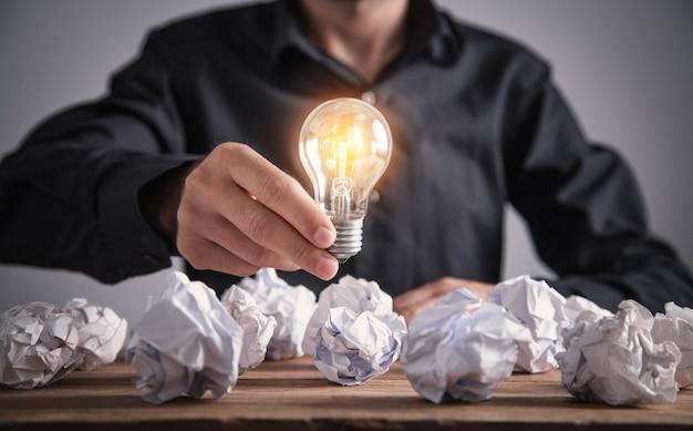 Uomo che tiene la lampadina, concetto di ispirazione e creatività