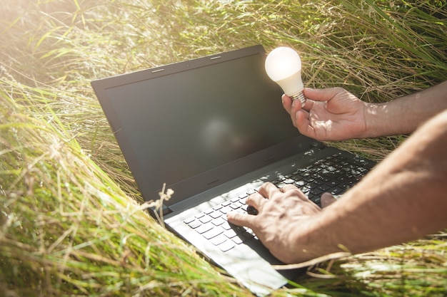 Uomo che tiene la lampadina e utilizzando il computer portatile in natura.