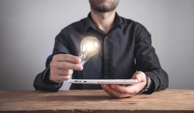 Uomo che tiene la lampadina con un tablet. ispirazione, tecnologia, creatività, affari