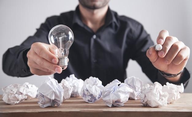 Uomo che tiene la lampadina e la scrittura sullo schermo. concetto di ispirazione e creatività