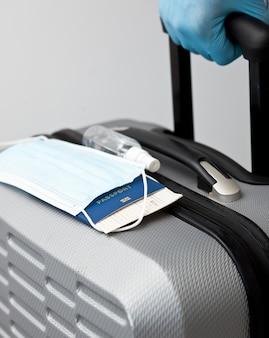 Uomo che tiene i bagagli con guanti in lattice