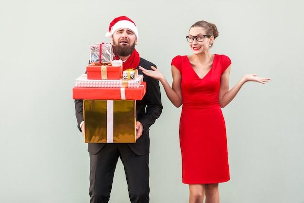 Uomo con molte scatole regalo e donne che piangono guardando la macchina fotografica sorridente e con le mani sui lati