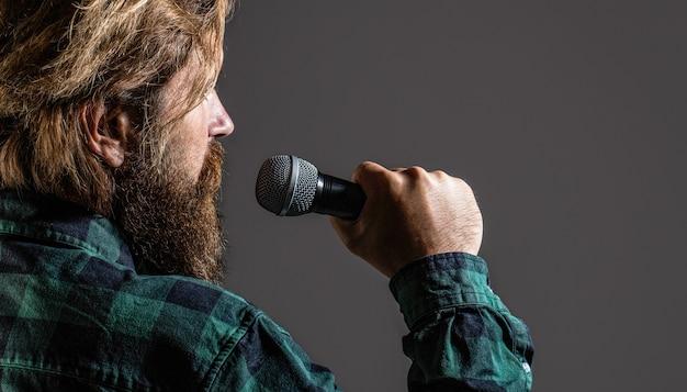 Uomo che tiene un microfono e canta. uomo barbuto che canta con il microfono. canto maschile con microfoni. l'uomo barbuto al karaoke canta una canzone in un microfono. il maschio frequenta il karaoke.