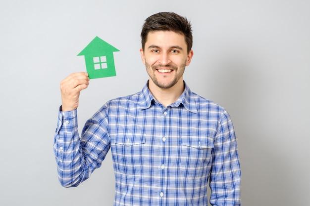 Uomo che tiene il modello di casa. l'acquisto di un concetto di casa