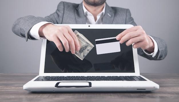Uomo che tiene soldi e carta di credito su un computer portatile.