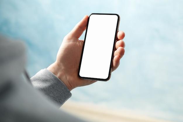 Equipaggi il telefono della tenuta con lo schermo vuoto contro fondo blu