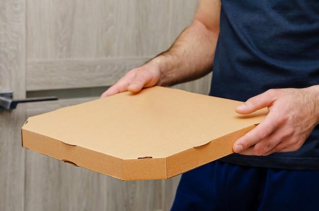 Uomo che tiene una scatola per pizza. ordine e consegna degli alimenti. copia spazio