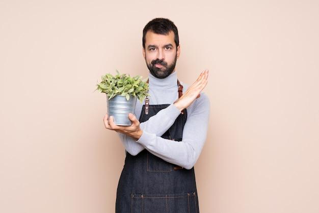 Uomo che tiene una pianta che non fa gesto