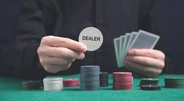 Uomo con fiches e carte del mazziere di poker sul tavolo verde.