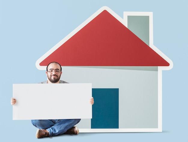 Man holding poster con casa modello