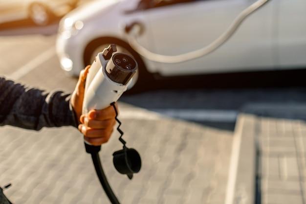 Uomo che tiene il cavo di ricarica per auto elettriche nel parcheggio all'aperto