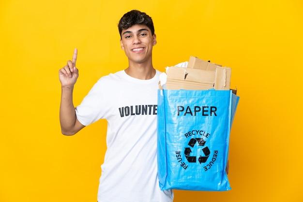 Uomo che tiene un sacchetto di riciclaggio pieno di carta da riciclare sopra fondo giallo isolato che indica una grande idea