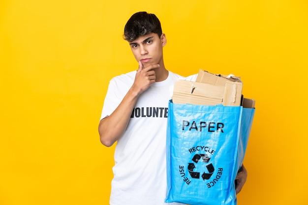 Uomo che tiene un sacchetto di riciclaggio pieno di carta da riciclare sopra il pensiero giallo isolato del fondo