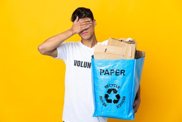 Uomo che tiene un sacchetto di riciclaggio pieno di carta da riciclare sugli occhi di cono gialli isolati dalle mani. non voglio vedere qualcosa