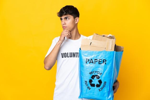 Uomo che tiene un sacchetto di riciclaggio pieno di carta da riciclare su giallo isolato e alzando lo sguardo