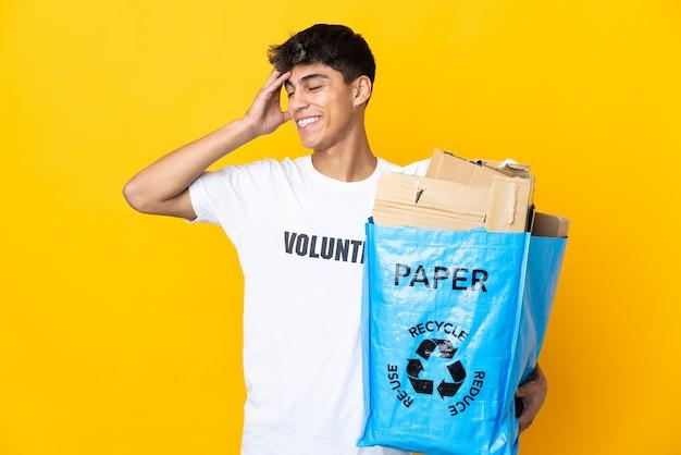 Uomo che tiene un sacchetto di riciclaggio pieno di carta da riciclare sul giallo isolato che sorride molto