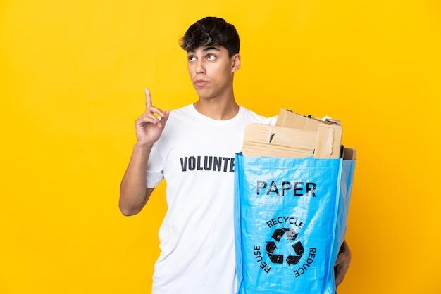 Uomo che tiene un sacchetto di riciclaggio pieno di carta da riciclare su giallo isolato pensando un'idea che punta il dito verso l'alto