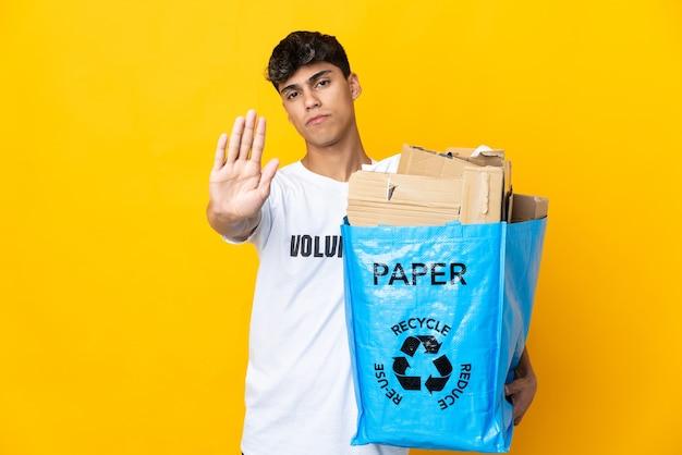 Uomo che tiene un sacchetto di riciclaggio pieno di carta da riciclare sopra la parete gialla isolata che fa gesto di arresto