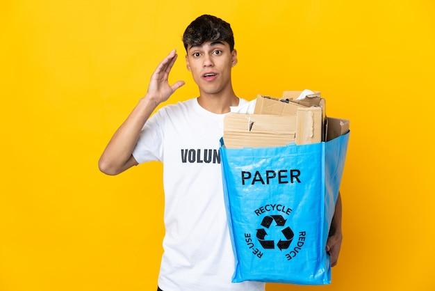 Uomo che tiene un sacchetto di riciclaggio pieno di carta da riciclare su giallo isolato con espressione facciale sorpresa e scioccata