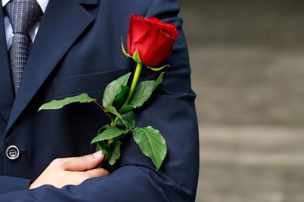 Uomo che tiene una rosa rossa in mano