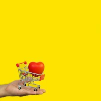 Uomo che tiene piccolo carrello con cuore rosso su sfondo giallo