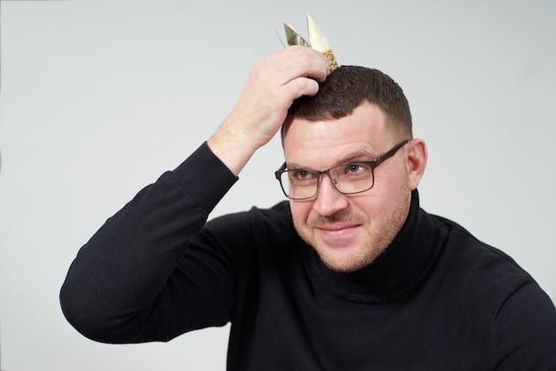 Uomo che tiene piccola corona sulla sua testa