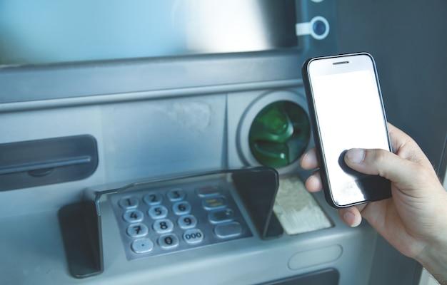 Uomo che tiene smartphone. atm. transazione online. concetto bancario
