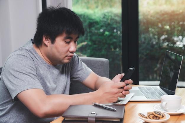 Un uomo che tiene uno smartphone in un angolo dell'ufficio domestico.
