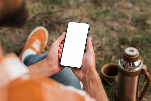 Uomo che tiene smartphone durante il campeggio all'aperto