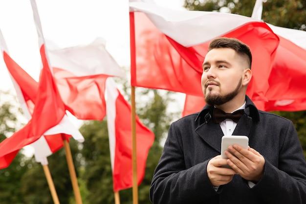 Equipaggi lo smartphone della tenuta con le bandiere della polonia dietro