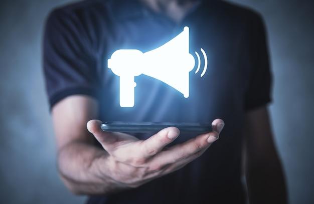 Uomo che tiene smartphone con un simbolo del megafono. attenzione. pubblicità e promozione. social media marketing