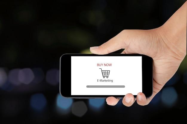 Uomo che tiene smartphone con lo shopping online. attività di commercio elettronico in linea. concetto di acquisto online.